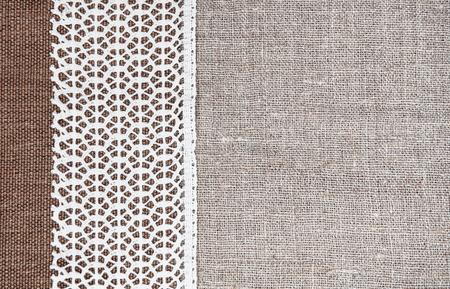 Uitstekende achtergrond met grof stof en kant op jute doek
