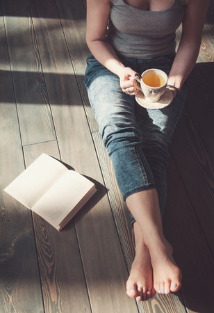 coffee and tea: Cozy photo of young woman with cup of tea sitting on the floor in sunlight