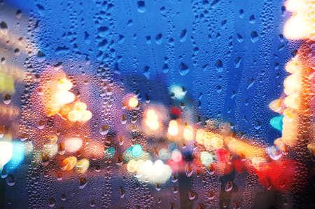 kropla deszczu: Krople deszczu na niebieskim szkła z rozmytym tle światła. Miejskie abstrakcyjne tło Zdjęcie Seryjne