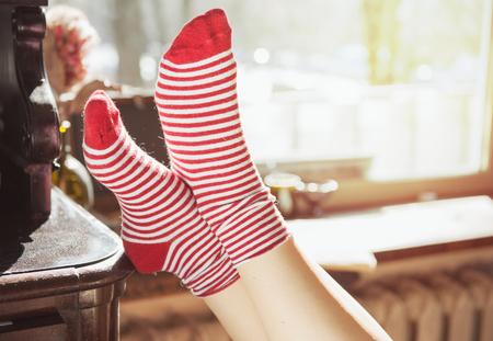 Pies de la mujer en calcetines rojos cerca de la ventana con la luz del sol Foto de archivo