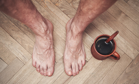 hairy male: Man feet on wooden floor and cup of coffee