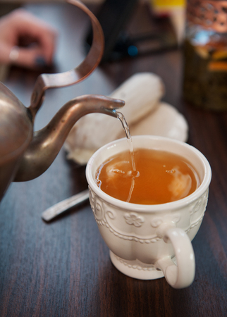 oldstyle: Old-style copper kettle pouring tea to white cup on wooden table