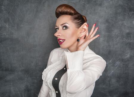 big ear: Woman with big ear eavesdropping on the blackboard background Stock Photo