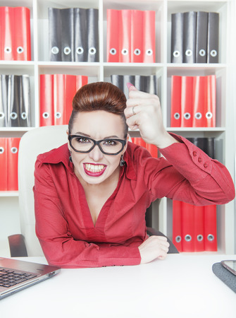 bawl: Angry screaming business woman shaking big fist in office