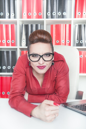 displeased: Angry displeased business woman with big fist in office Stock Photo