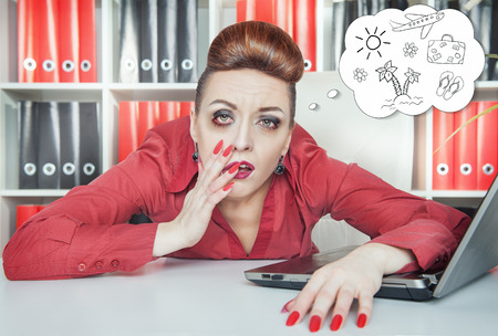 overwork: Tired bored businesswoman dreaming about holiday in office. Overwork concept