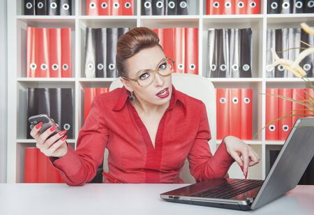 assiduous: Crazy business woman in glasses working with laptop