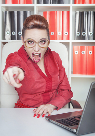 Angry crazy woman boss in eyeglasses pointing out at someone