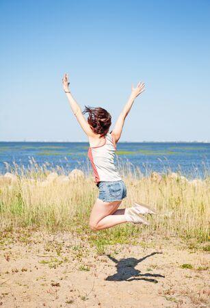 persona saltando: Mujer joven feliz que salta en la playa en verano Foto de archivo