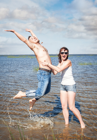 Happy young couple having fun in the water of sea outdoor