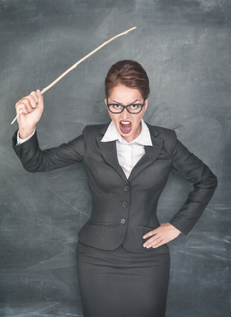 angry teacher: Angry teacher with wooden stick on chalkboard background