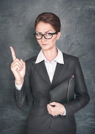 stringent: Strict teacher showing finger on the school blackboard background Stock Photo
