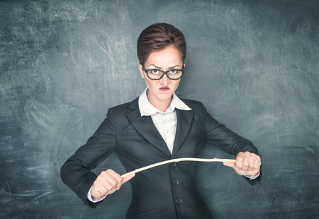 grouch: Angry teacher in glasses with wooden stick on chalkbooard background