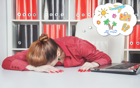 Tired businesswoman sleeping on the table and dreaming about vacation in office photo