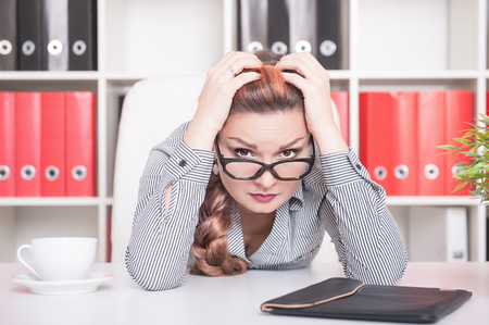 hard day at the office: Tired beautiful business woman in glasses working in office Stock Photo