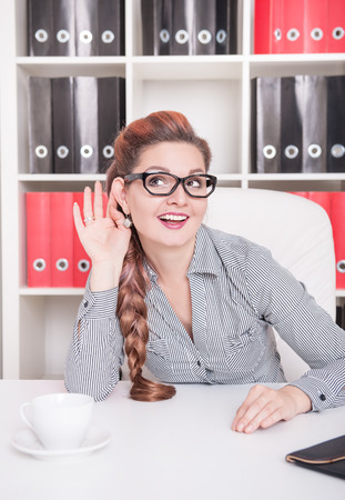eavesdropping: Beautiful smiling business woman eavesdrop in the office