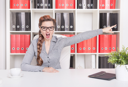 dismissal: Angry business woman boss pointing out in office. Dismissal concept Stock Photo