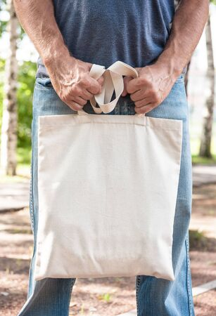 Man holding empty canvas bag outdoor. Template mock up