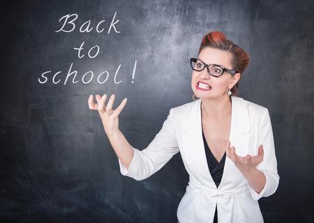 angry teacher: Angry teacher in glasses on chalkboard blackboard background