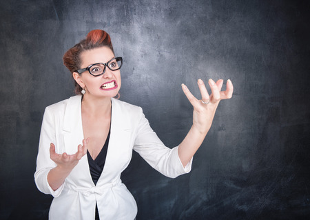 exasperation: Angry teacher in glasses on chalkboard blackboard background