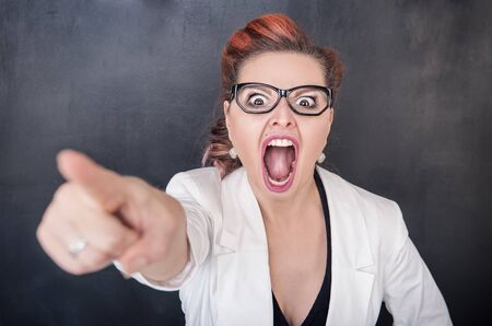 bawl: Angry screaming woman pointing out on chalkboard blackboard background Stock Photo
