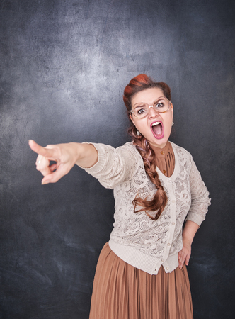 bawl: Angry screaming teacher pointing out on chalkboard blackboard background