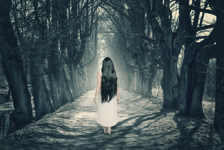 Halloween mystical forest with ghost on the road Stock Photo