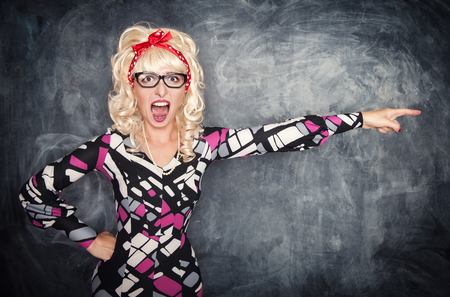 Angry screaming retro teacher pointing out on chalkboard blackboard background Stock Photo