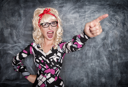 expel: Angry screaming retro teacher pointing out on chalkboard blackboard background Stock Photo