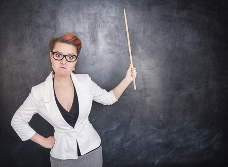 Angry teacher with pointer on the chalkboard blackboard background Stock Photo