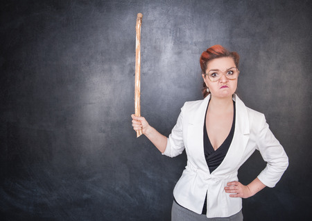 angry teacher: Angry teacher with pointer on the chalkboard blackboard background Stock Photo