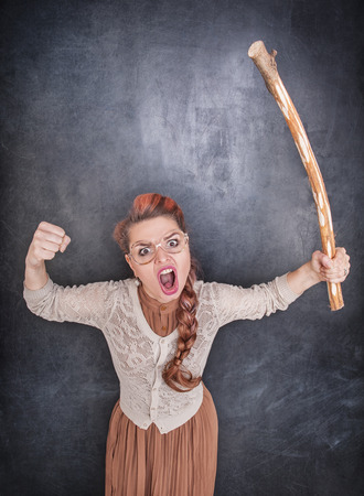 bawl: Angry screaming teacher with wooden stick on chalkboard blackboard background