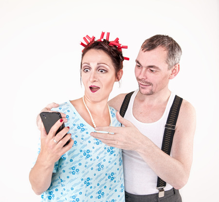 Funny happy family couple using smartphone on white