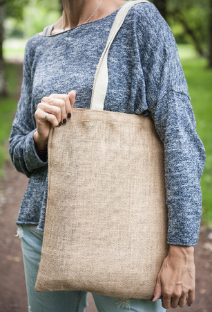 Woman holding empty canvas bag outdoor. Template mock up Stock Photo
