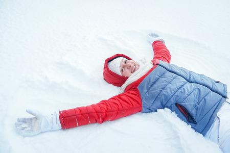 Glückliche junge Frau, die Spaß auf Schnee im Winter