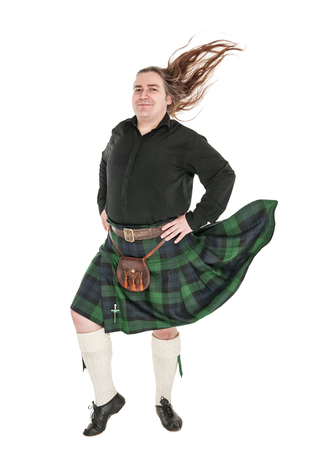 Scottish man in traditional national costume with blowing kilt isolated