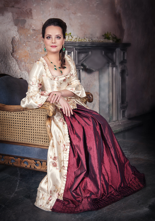 ruche: Beautiful woman in old historic medieval dress sitting in the chair