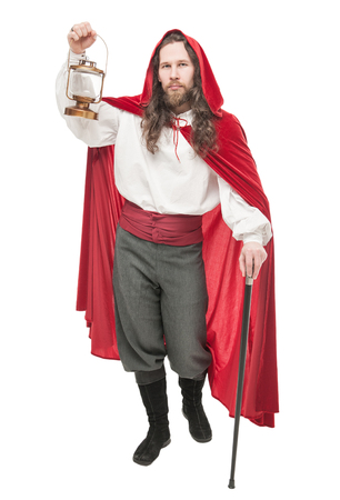 Medieval man in cape with cane and lamp isolated on white Stock Photo