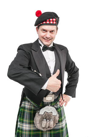 Young man in clothing for Scottish dance showing thumbs up isolated