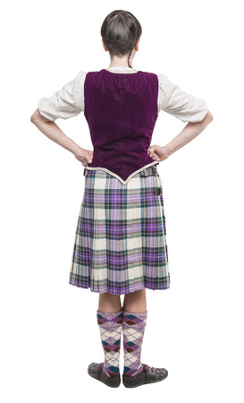 Young woman in traditional clothing for Scottish dance isolated. Back pose