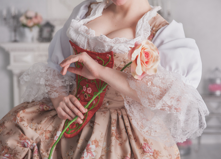 ruche: Beautiful woman in medieval dress holding pink rose