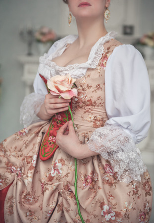 ruche: Beautiful woman in old medieval dress holding pink rose