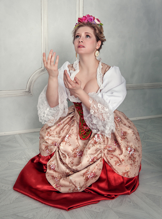 Beautiful medieval woman in historic old-fashioned dress praying