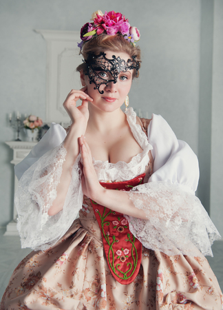 Beautiful woman in old-fashioned historic medieval dress with mask
