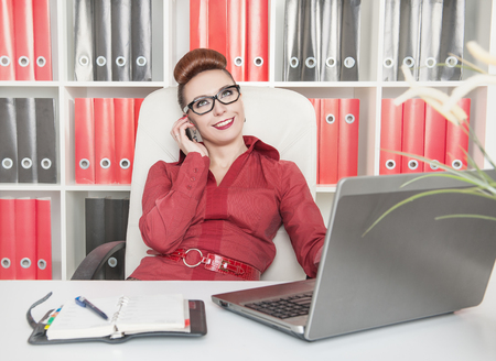Happy business woman using mobile phone and working with laptop in office photo