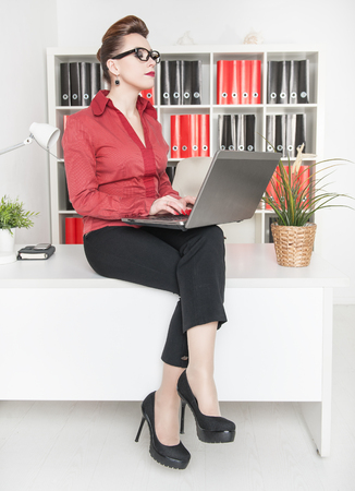 Beautiful business woman working and sitting on table in office photo
