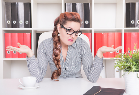 Business woman shrugging her shoulders working in office