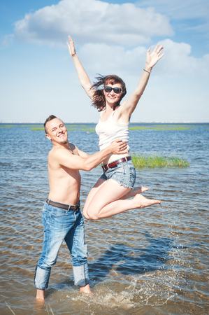 Happy young couple having fun in the water of sea outdoor photo