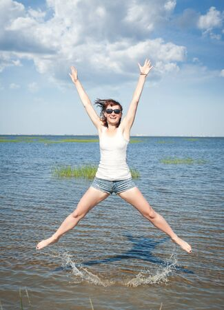 Happy young woman having fun in water of sea outdoor photo