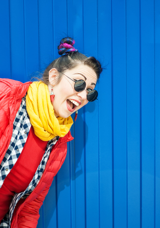 Young beautiful fashion hipster woman with colorful hair over blue background